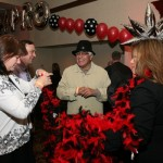 Gracie Vega distributes feather boas HATC Casino Night